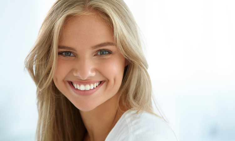 Blonde woman with a beautiful white smiles because it was cleaned using professional dental tools