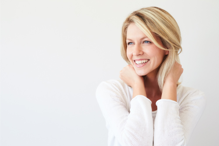 Blonde woman smiles with dental implants and a white blouse